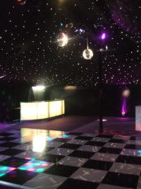 Black and white dance floor and illuminated bar